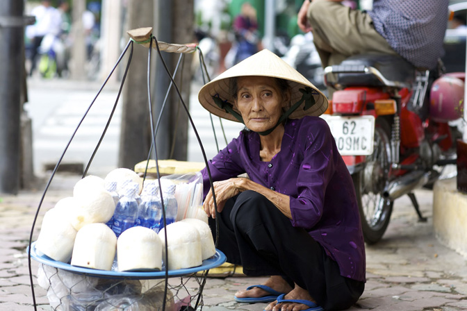 <p>Unidentified woman street vendor in Ho Chi Minh City, Vietnam selling coconuts and water on June 2, 2008</p>