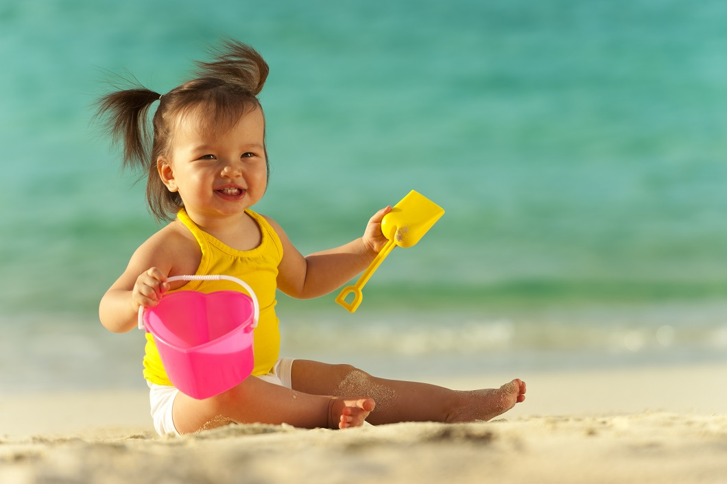 Baby girl playing on the beach