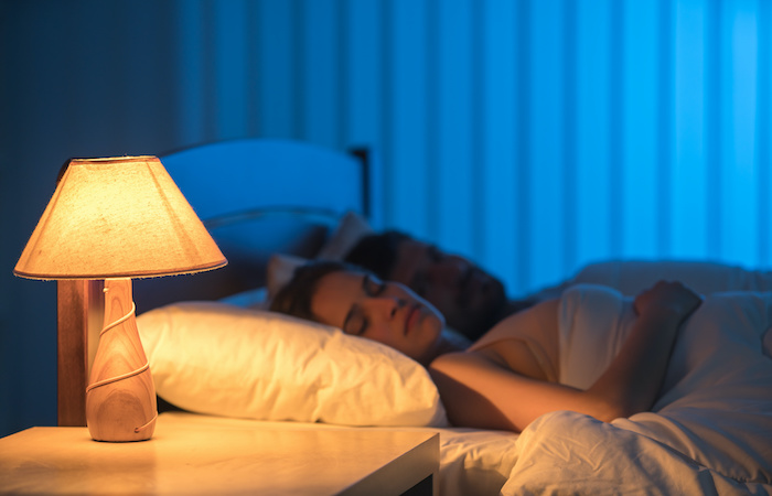 couple sleeping with lamp on fertility home treatments