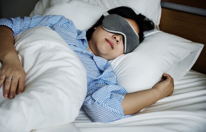 woman sleepign well in bed, with no sleep disorders or snoring