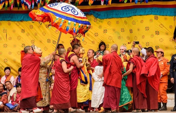Laughing red-robed monks at a festival in Bhutan, to illlustrate secrets of a happy life, the world'a happiest countries.