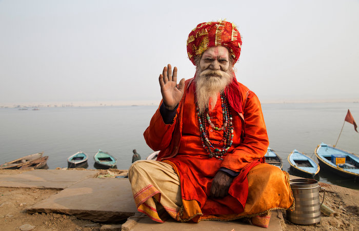 Smiling Indian spiritual guru in orange robes sitting by a river, for lessons from the world's happiest countries