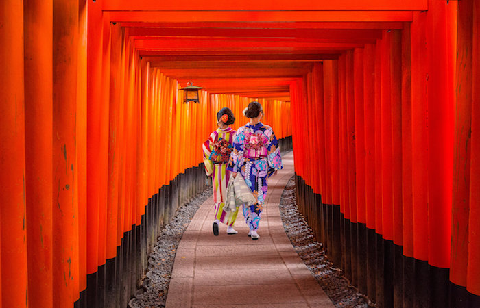Two geisha in kimono walk under red tori gates in Japan, to show secrets of a happy life, the world's happiest countires