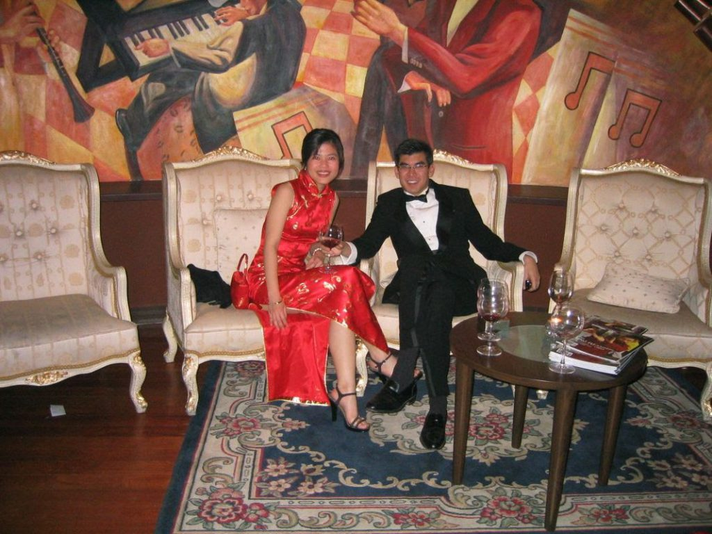 International love: Oliver and Candy Kuan dressed for a wedding, She is wearign a red qipao, he wears a velvet dinner jacket