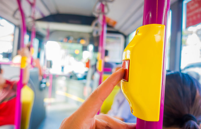 Getting around Singapore - pressing a bus stopping sign on a bus in singapore