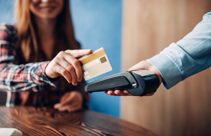 woman paying with credit card for article on saving money in singapore