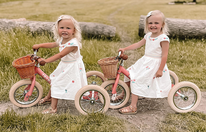 2 little blond girls on tricycles, in Frugi sustainable kids clothes from the UK