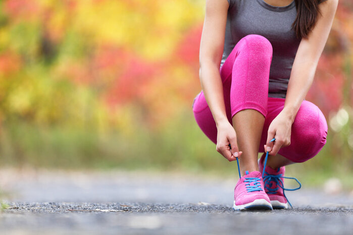 women in pink  leggings lacing up her trainers to go for a run