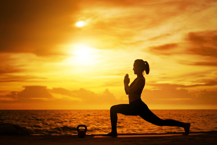 silhouette of women doing yoga at sunset as part of self improvement programme