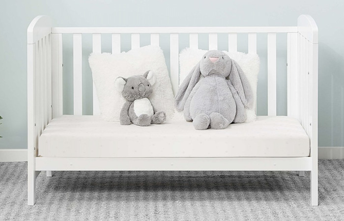Stuffed toys and a toddler's white wooden bed, at childrens furniture store in SIngapore, Motherswork