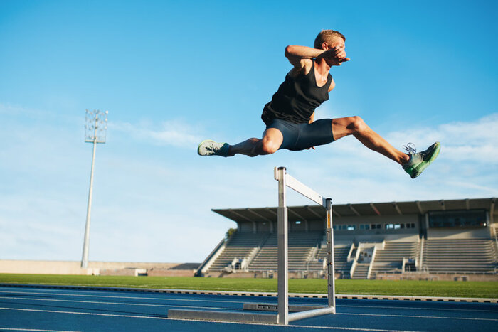 man jumping over hurdle, to symbolise overcoming barriers to self improvement