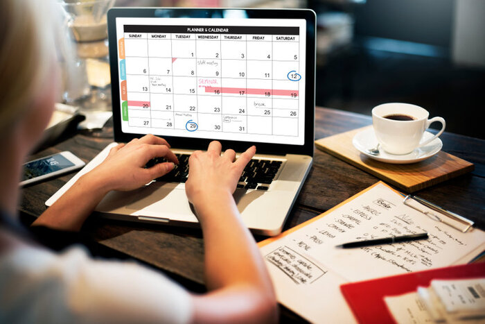 woman filling in calendar on laptop, to chart her self improvement goals