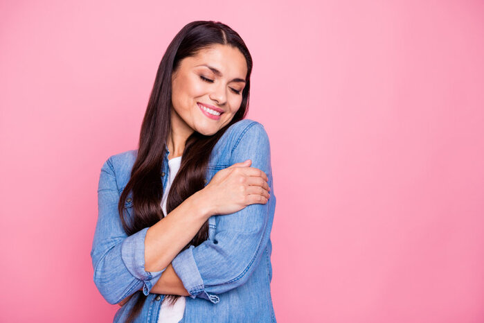 asian woman with long dark hair hugging herself, to show how being kind to yourself helps with self improvement