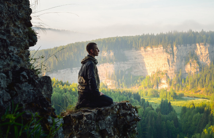 man in the mountains practicing mindfulness